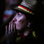 German fan keeps hand in prayer gesture as she watches a FIFA World Cup 2014 game between Germany and Ghana, broadcast at a large public viewing area in Freiburg, Germany. Final score 2-2 on June 21.