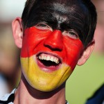 German football fan with black-red-gold face paint cheers as he watches the FIFA World Cup 2014 game between Germany and USA, broadcast at a large public viewing area in Freiburg. Germany wins 1-0 on June 26.