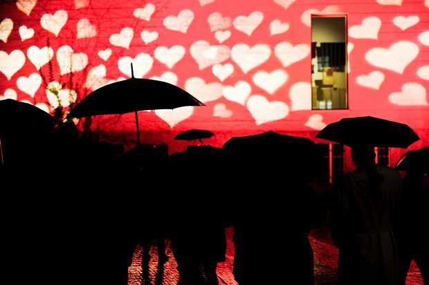 Visitors with umbrellas observe an outdoor lighting show in front of the Museum of Cultures in Basel. January 16, 2015.