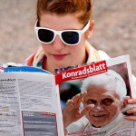 A teenager reads about the upcoming visit of Pope Benedikt XVI in Freiburg, Germany. September 24, 2011.